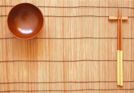 Chopsticks with wooden bowl on bamboo matting background Stock Photo