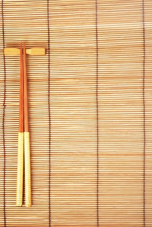 Chopsticks on brown bamboo matting background
