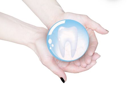 hands holding tooth in glass sphere, dentistry   photo