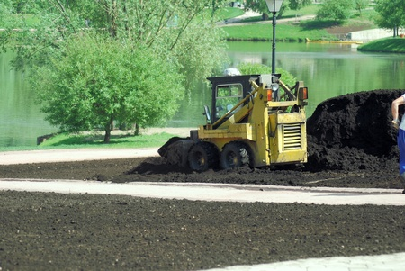 Mini excavator-grab working in city park  at the spring
