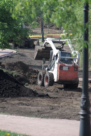 mini wheel excavator working in city park at the spring