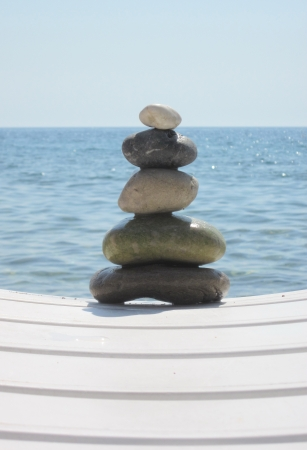 The stack of pebble stones in zen concept  on chaise longues  photo