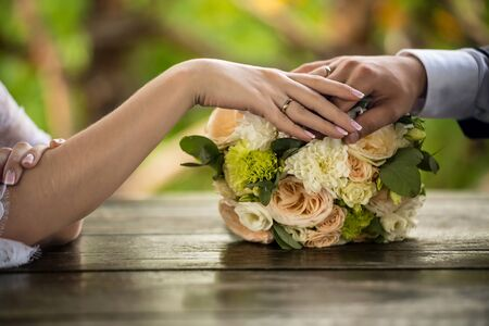 Hands of the bride and groom on a wedding bouquet. Close-up. Wedding rings in focus. Bouquet on a wooden table. Horizontal frame.