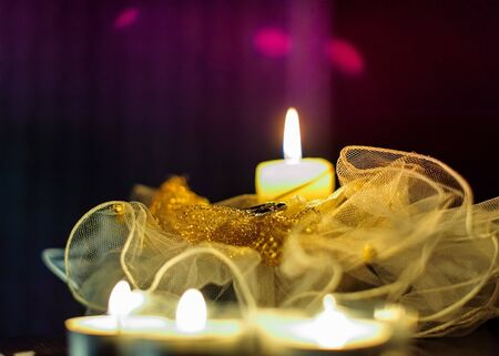 Wedding rings, candles. Lace with gold embroidery. Light from a candle. Imagens