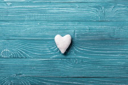 Knitted heart on a blue wooden background
