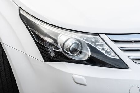 Closeup headlamp of a white luxury car.- Image