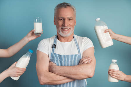 Handsome, smiling man is standing on a blue background, with people's hands holding milk around him, as if offering him. Man with crossed arms.