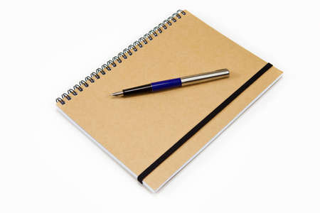 Brown Spiral Notebook With Fountain Pen On Isolated White Border photo