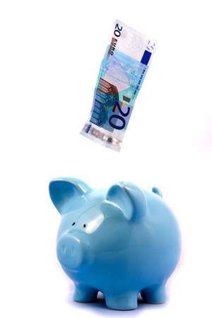Note Falling into Blue Piggy Bank on White Background Stock Photo