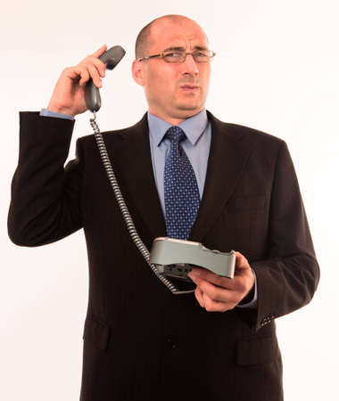 Businessman speaking to angry customer on the telephone Stock Photo