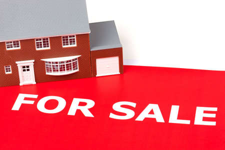 House sitting on a large red for sale sign Stock Photo - 7485544