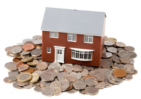 A family house sat on a pile of loose coins