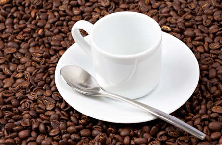 White espresso cup sat on coffee beans with silvered colored spoon Stock Photo