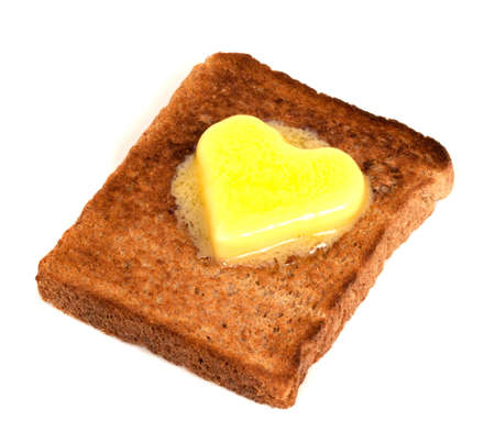 Melting Heart Shaped Butter on wholemeal Toast on white background