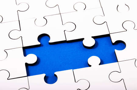 White Jigsaw with two pieces missing with blue underneath Stock Photo
