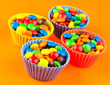 Bright colred sweets in cup cake holders on an orange background