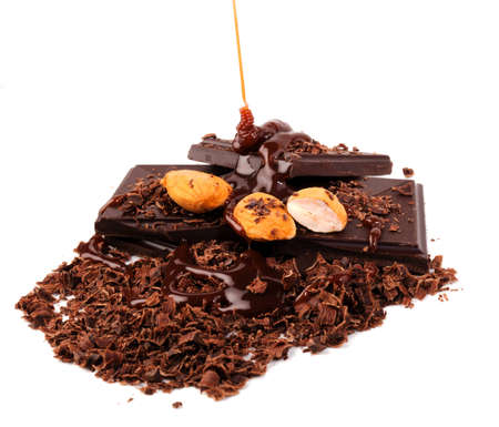Pieces of chocolate with almonds and shavings with syrup being poured over