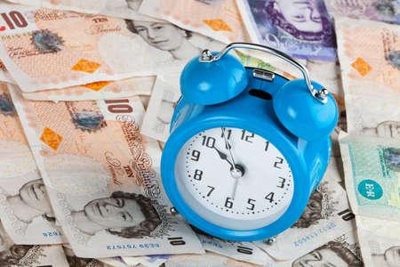 Blue alarm clock sat of uk stirling bank notes Stock Photo