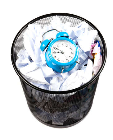 Blue alarm clock sat in a waster paper basket Stock Photo