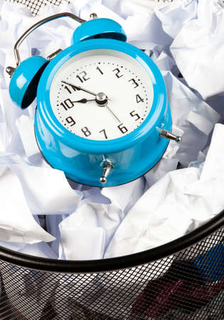 close up of Blue alarm clock sat in a waster paper basket  Stock Photo
