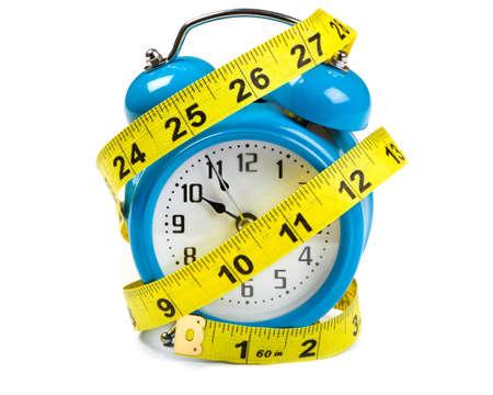 Tape Measure  wrapped around a blue alarm clock