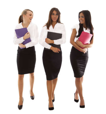 three business woman walking together all carrying document folders Stock Photo