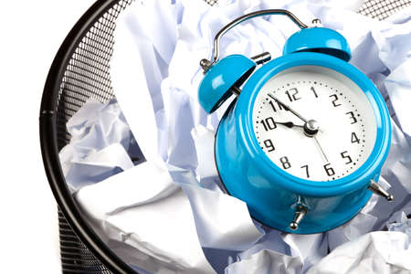 Old fashioned two bell alarm clock in waste paper basket
