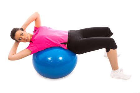 a girl performing an ab crunch on a blue gym ball Stock Photo