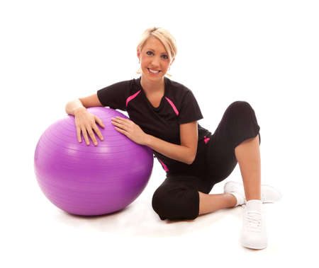 A gril sat on the floor resting a on a purple gym ball photo