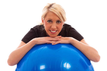 A girl leaning over a blue gym ball on isolated white background Stock Photo