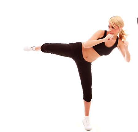 martial arts woman: A young female dressed in black gym clothes performing a karate kick on isloated white background