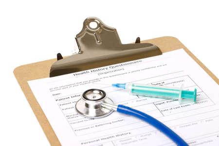 Un portapapeles con un formulario de historia médica con una jeringa y un estetoscopio sobre fondo blanco isloated Foto de archivo