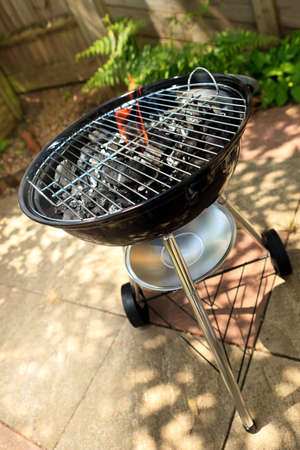 a traditional style bbq  with flames coming through the grill Stock Photo