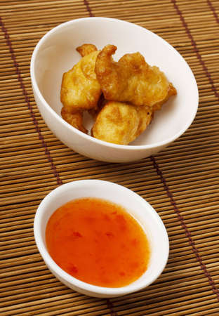 Chicken deep fried in batter with a Sweet and Sour dipping sauce photo