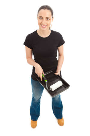 A young female dressed in a black t shirt and blue jeans holding a paint roller and tray Stock Photo - 9987513