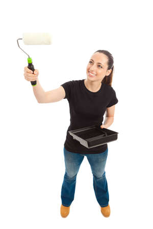 A young female dressed in a black t shirt and blue jeans holding a paint roller and tray photo