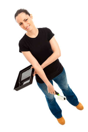 A young female dressed in a black t shirt and blue jeans holding a paint roller and tray Stock Photo - 9987522