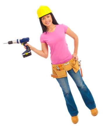 Een jong wijfje gekleed in jeans en roze hoogste en gele bouwvakker die een draadloze boor houden