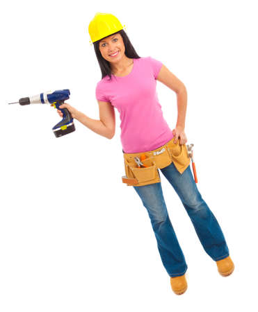 Une jeune femme habillée en jeans bleu et rose jaune et haut casque tenant une perceuse sans fil