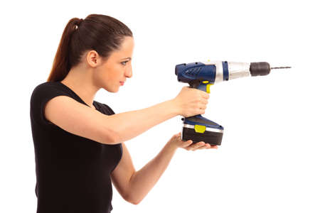 Young female dressed in black top holding a cordless electric drill on a white isolated background photo