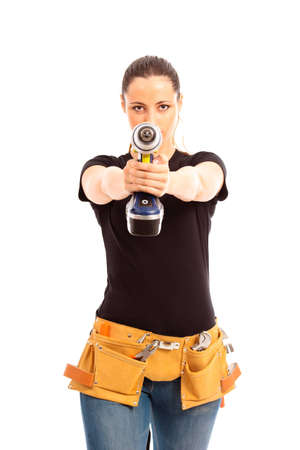 Young female dressed in black top blue jeans waering a tool belt holding a cordless electric drill on a white isolated background