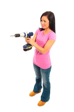 Young female dressed in pink top and blue jeans holding a cordless electric drill on isolated white background. photo