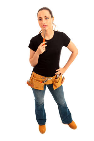 Young female dressed in black top blue jeans waering a tool belt holding a screwdriver on a white isolated background Stock Photo