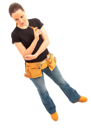 Young female dressed in black top blue jeans waering a tool belt holding a cordless electric drill on a white isolated background Stock Photo - 10106504