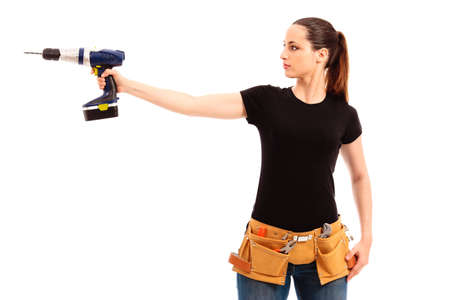 Young female dressed in black top blue jeans waering a tool belt holding a cordless electric drill on a white isolated background photo