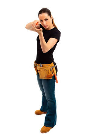 a young female dressed in blue jeans and black top and tool belt holding a screwdriver on isolated white background
