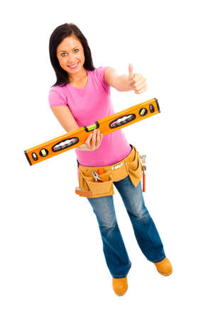 a young female wearing pink top blue jeans and tool belt holding a spirit level on isolated white background Stock Photo