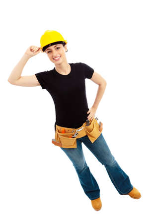 a young female dressed in blue jeans and black top and tool belt and yellow hardhat  on isolated white background Stock Photo