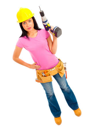 a young female wearing pink top blue jeans and tool belt holding an electric drill on isolated white background