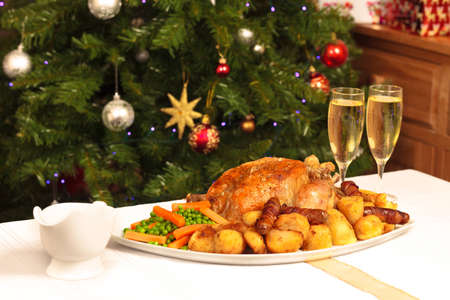 christmas turkey: A platter containing a christmas dinner with a christmas tree in the background Stock Photo